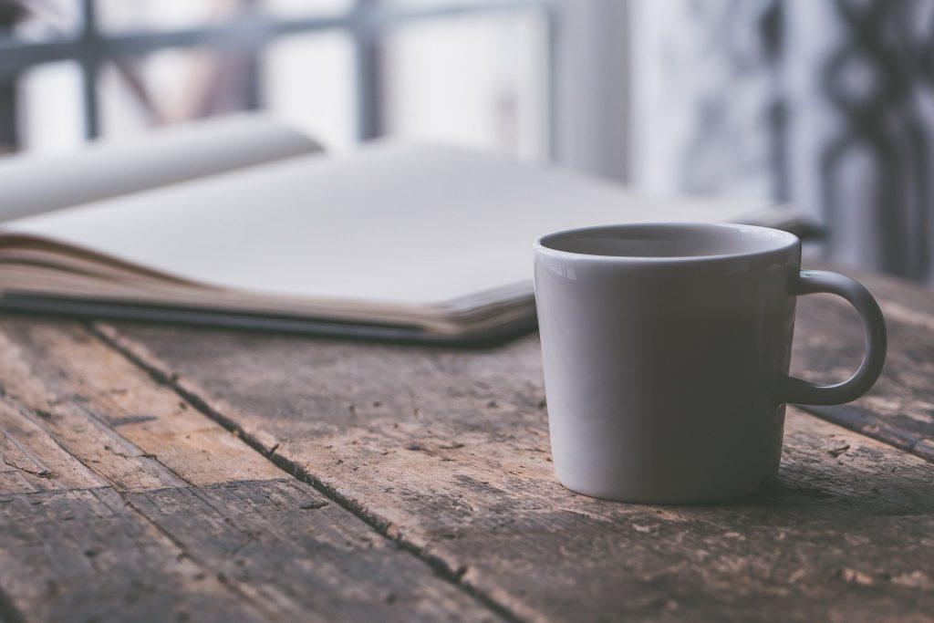cahier avec tasse blanche de café