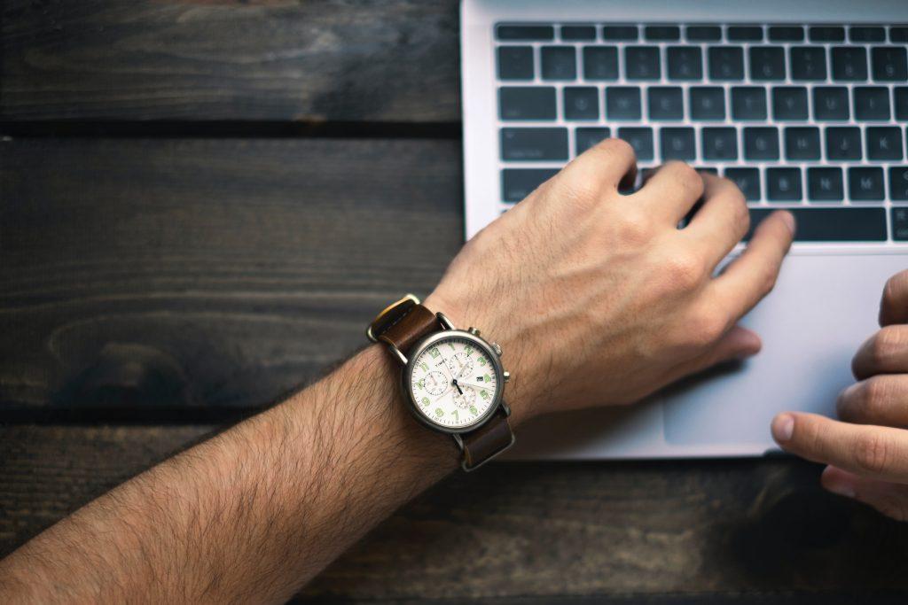 main homme avec montre sur ordinateur