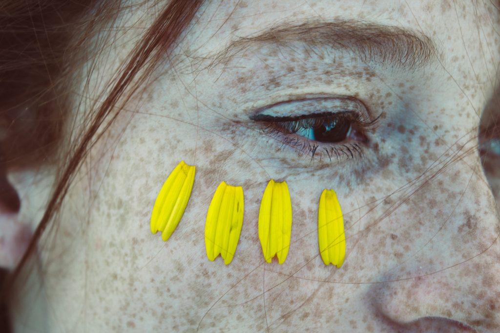 oeil femme taches de rousseurs et pétales de fleur jaunes