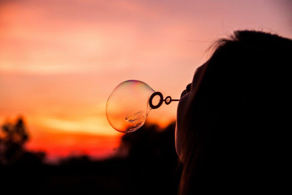 fille de dos qui souffle une bulle