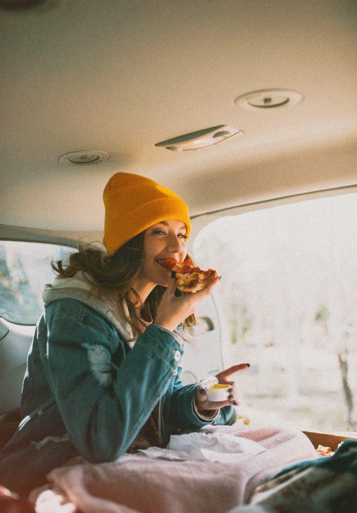 femme tuque jaune mange pizza