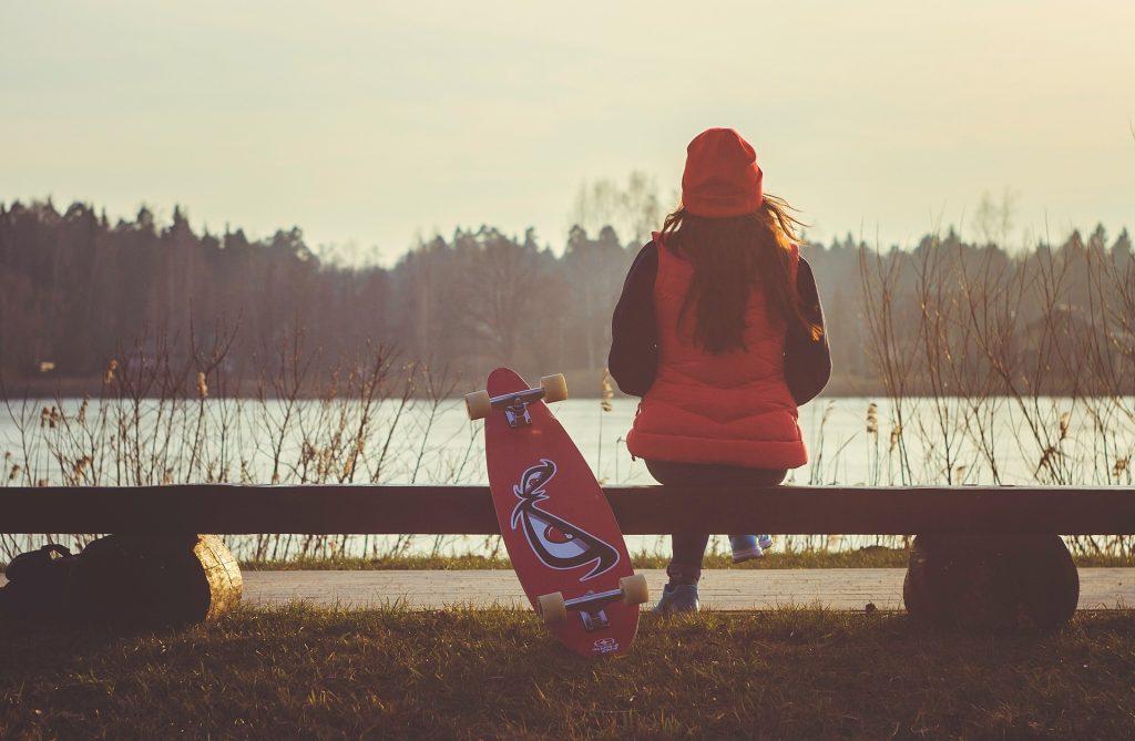 fille de dos devant eau avec skate