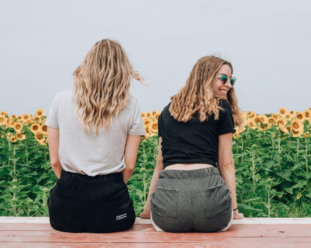 filles assises de dos champ de tournesols