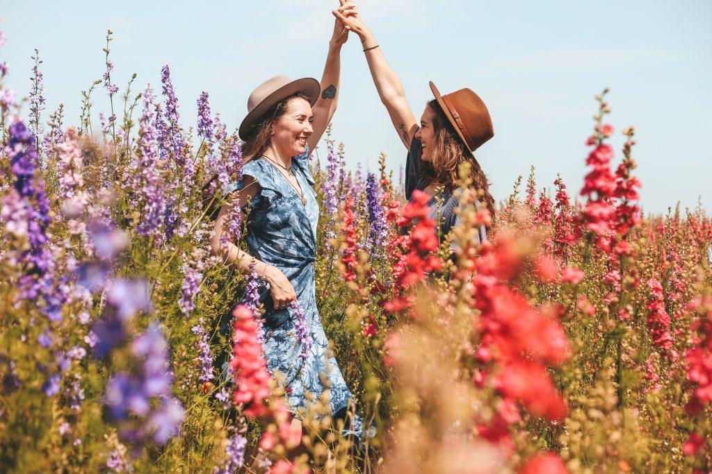 femmes main dans la main champ de fleurs