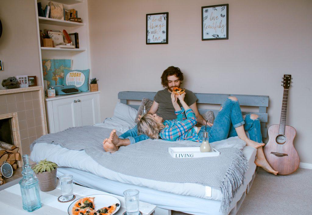 femme couchée donne pizza lit