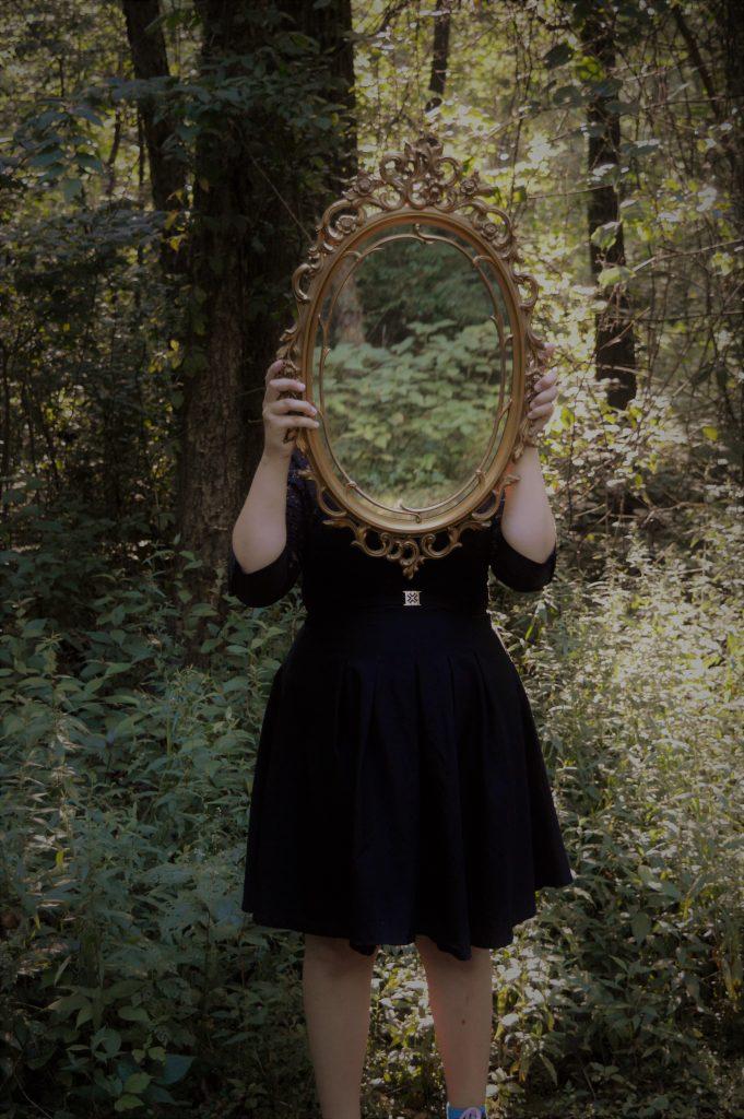 femme robe noire tient miroir forêt
