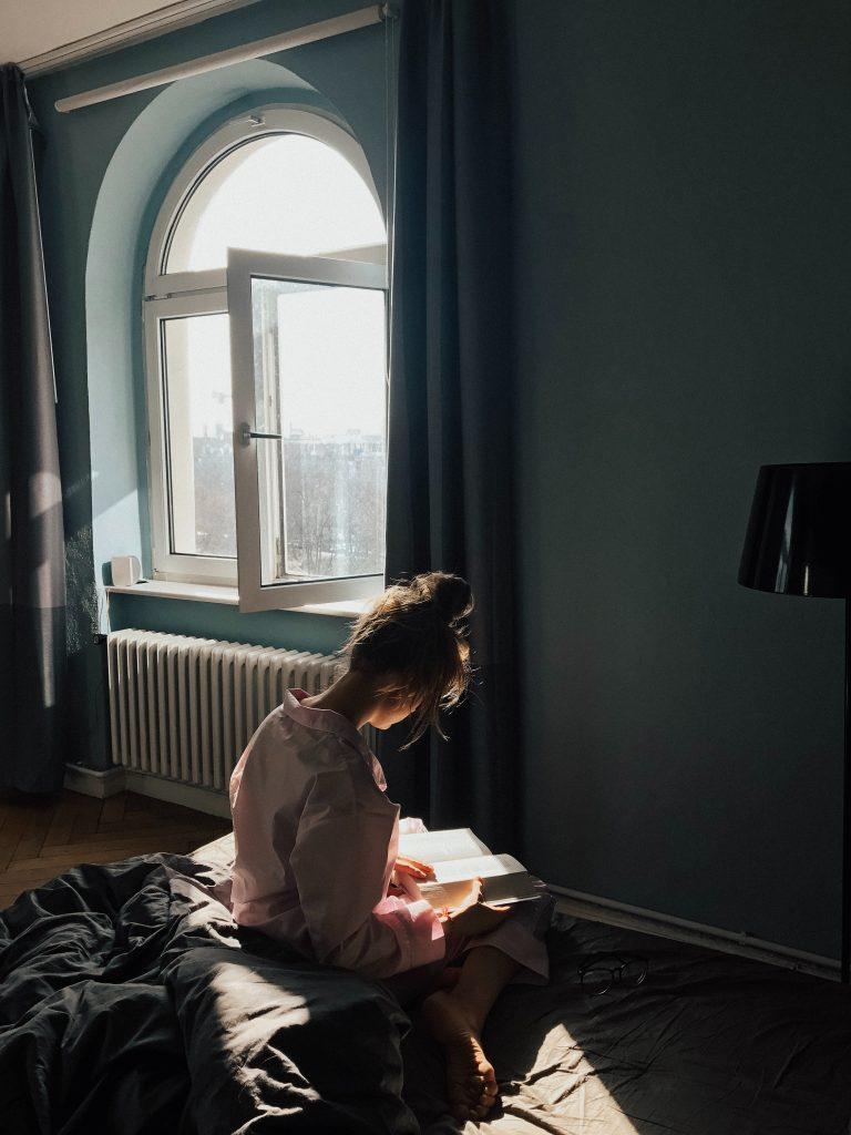 femme seule près d'une fenêtre qui lit