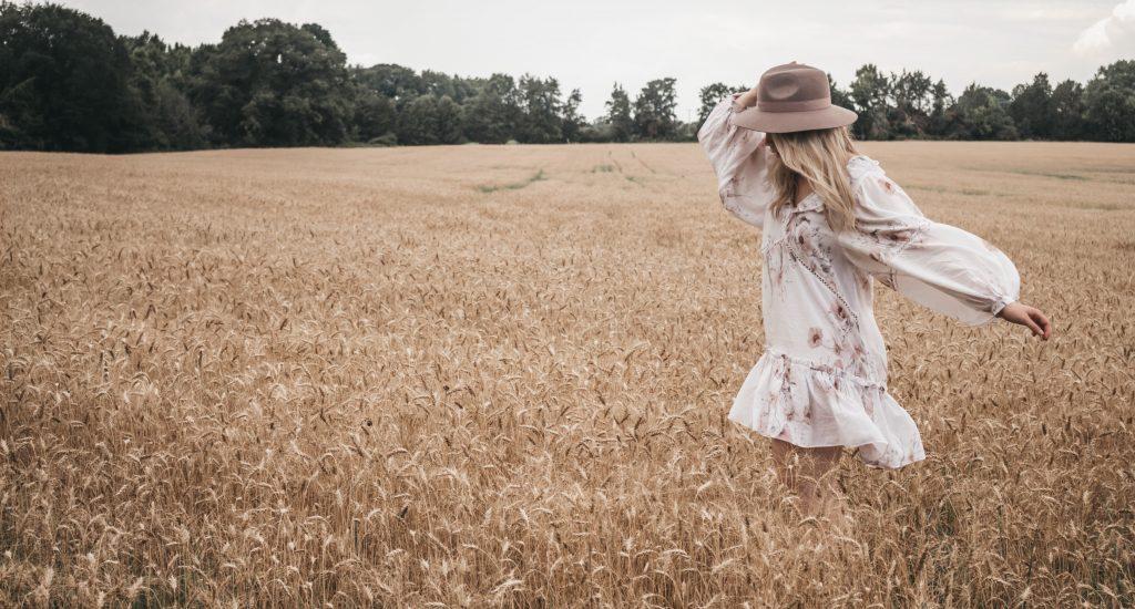 femme en robe fleurie qui court dans champ