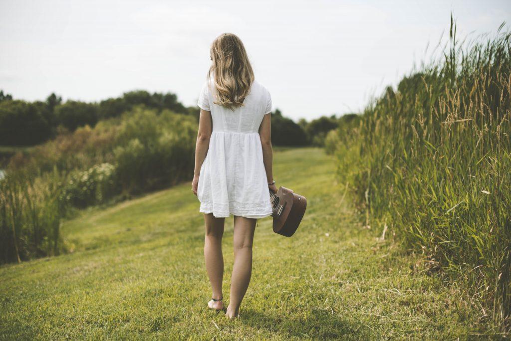 femme robe blanche de dos herbes et ukulélé