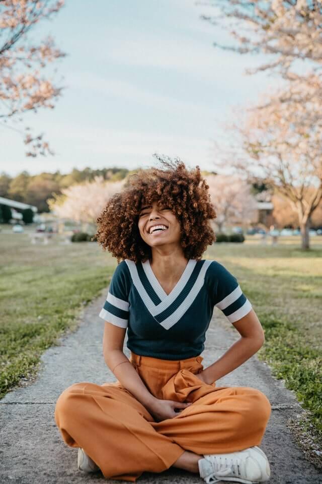 femme cheveux frisés heureuse sourire