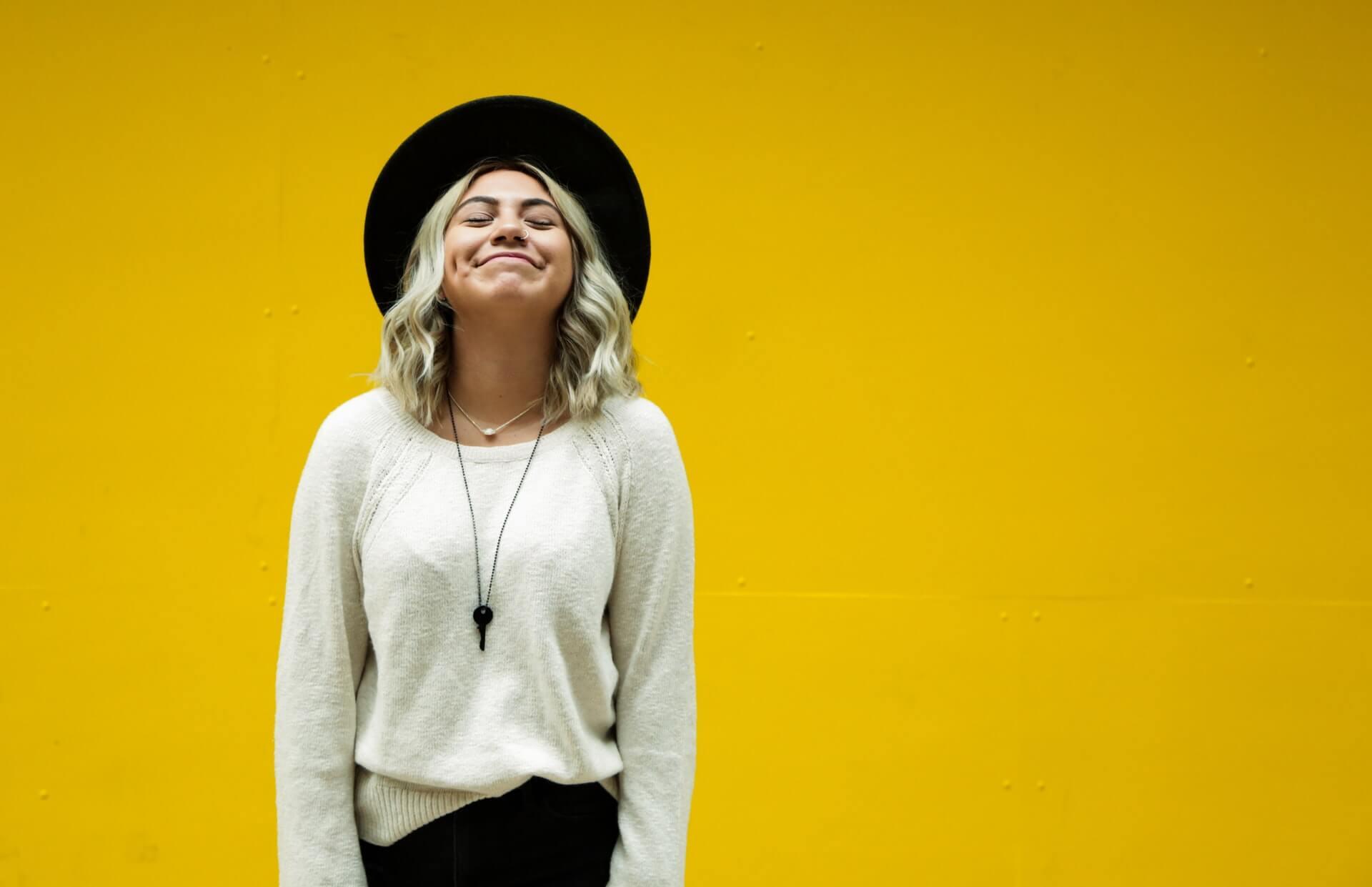 mur jaune fille chapeau sourire contente