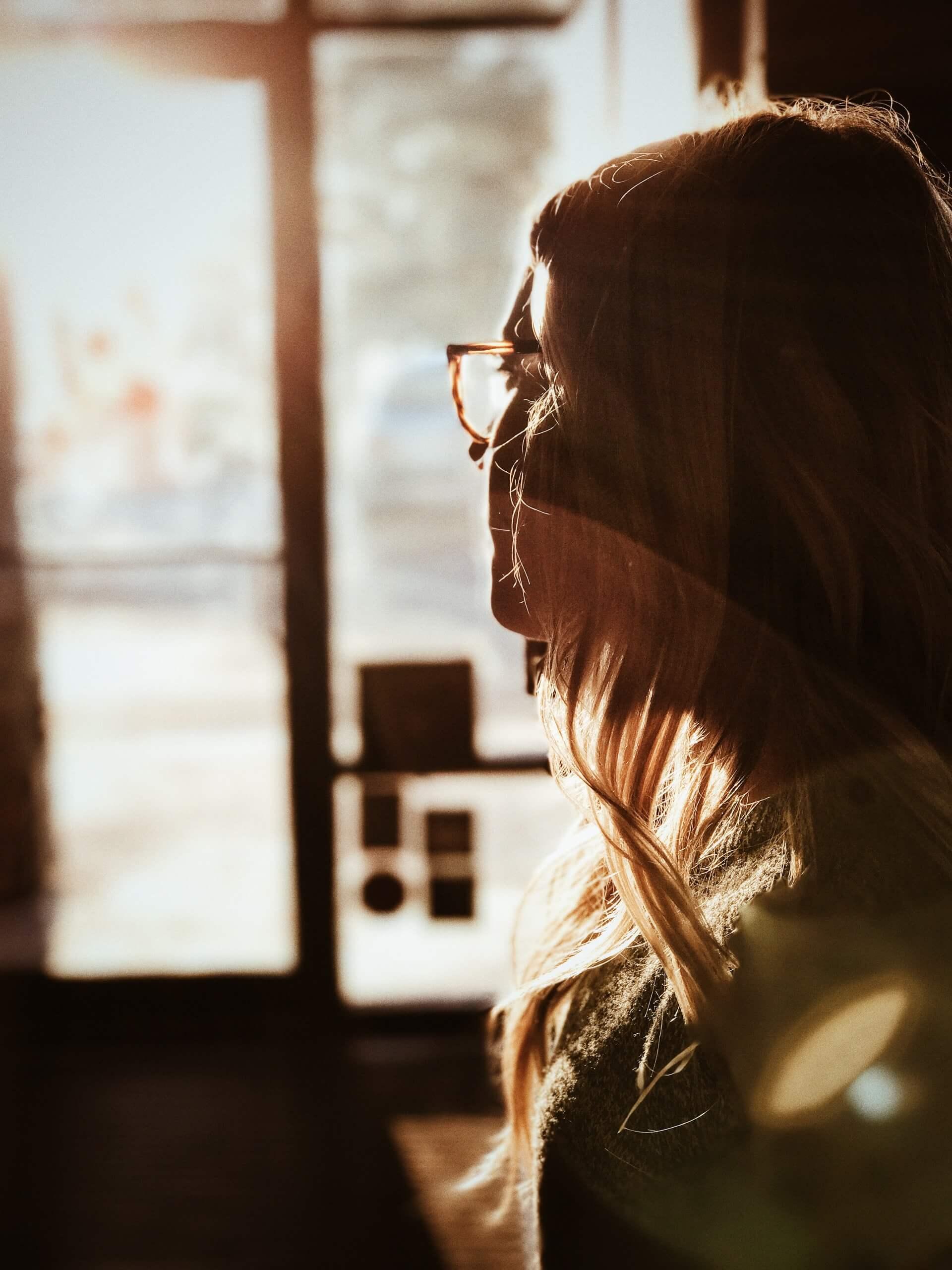 femme regardant en direction de la fenêtre