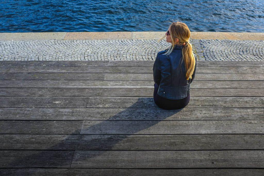 fille assise sur le bord de l'eau