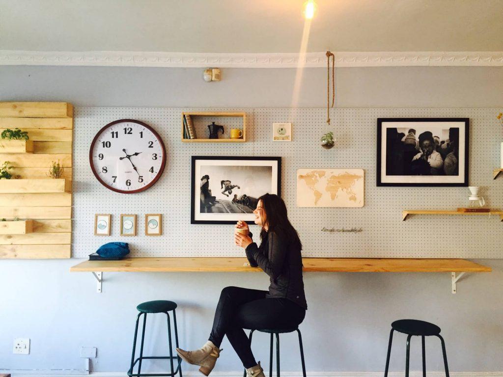 femme assise devant un mur avec plusieurs cadres