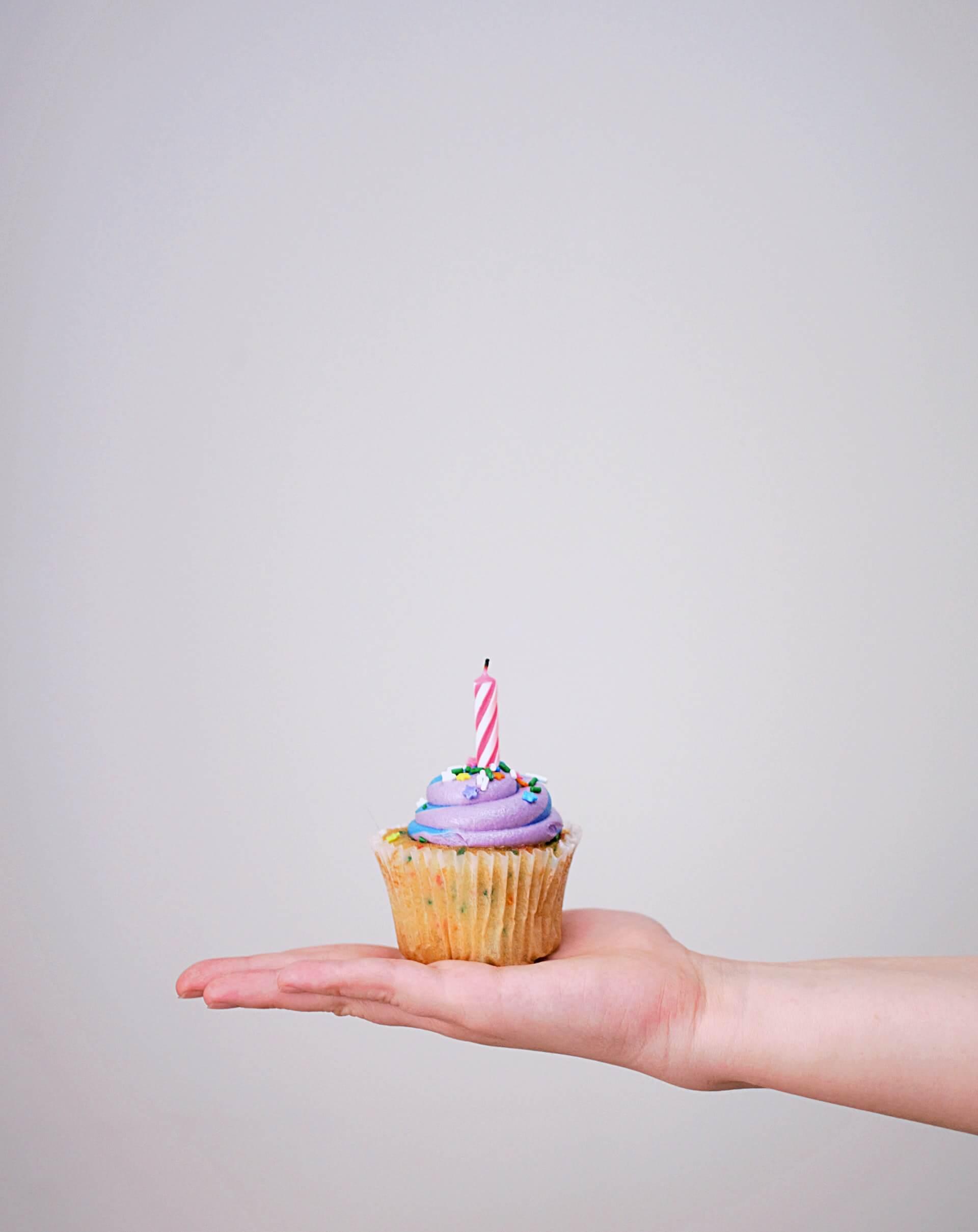 un cupcake d'anniversaire dans une main