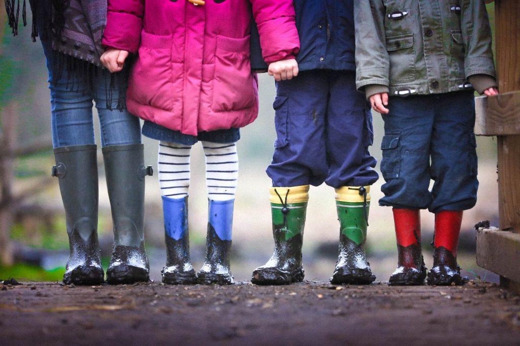Enfants dehors bottes de pluie boue amis