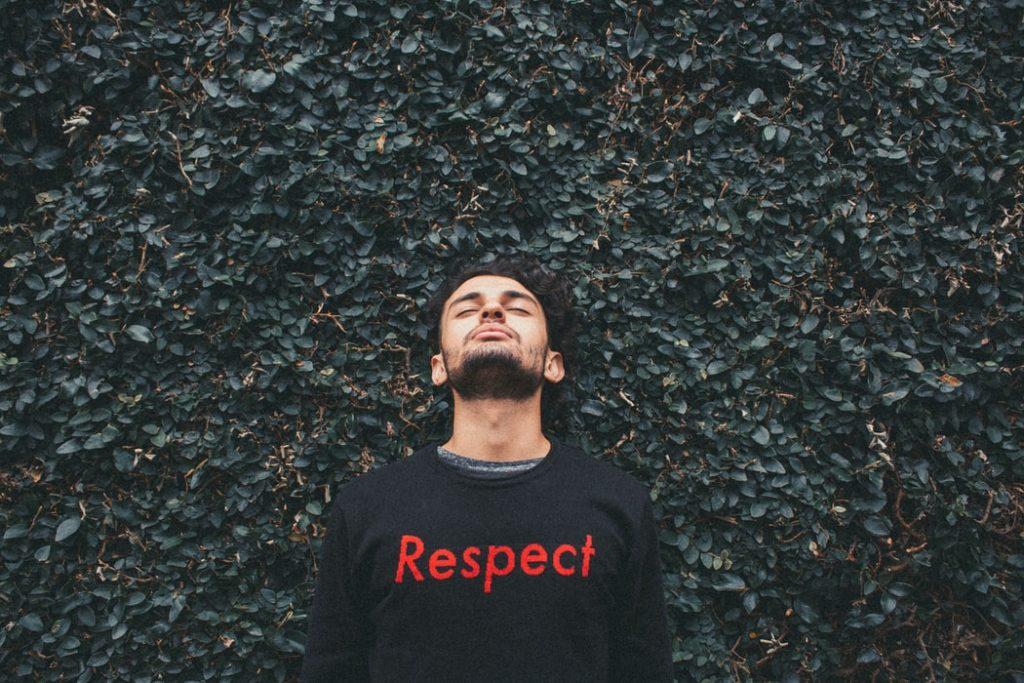 Homme debout derrière des plantes à feuilles vertes, portant un chandail avec le mot Respect