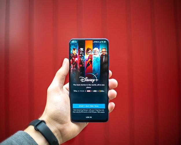Personne tenant un iPhone avec l'application Disney+