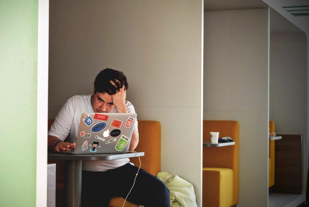 Homme portant un haut blanc utilisant un MacBook