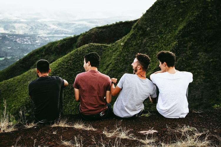 Rangée de quatre hommes assis sur un sentier de montagne