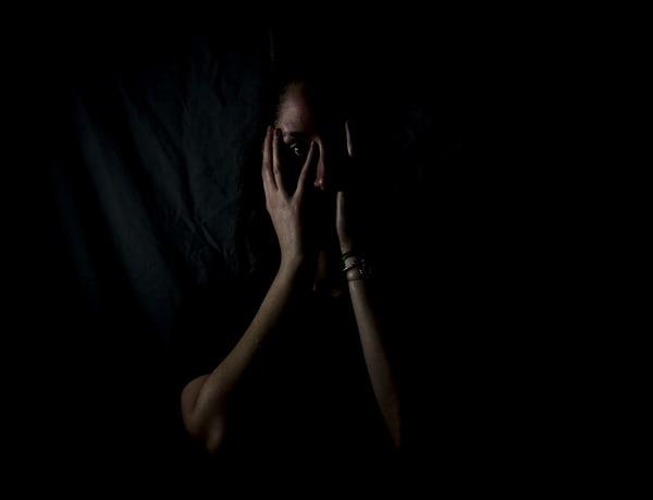Femme fond noir visage caché par mains peurs