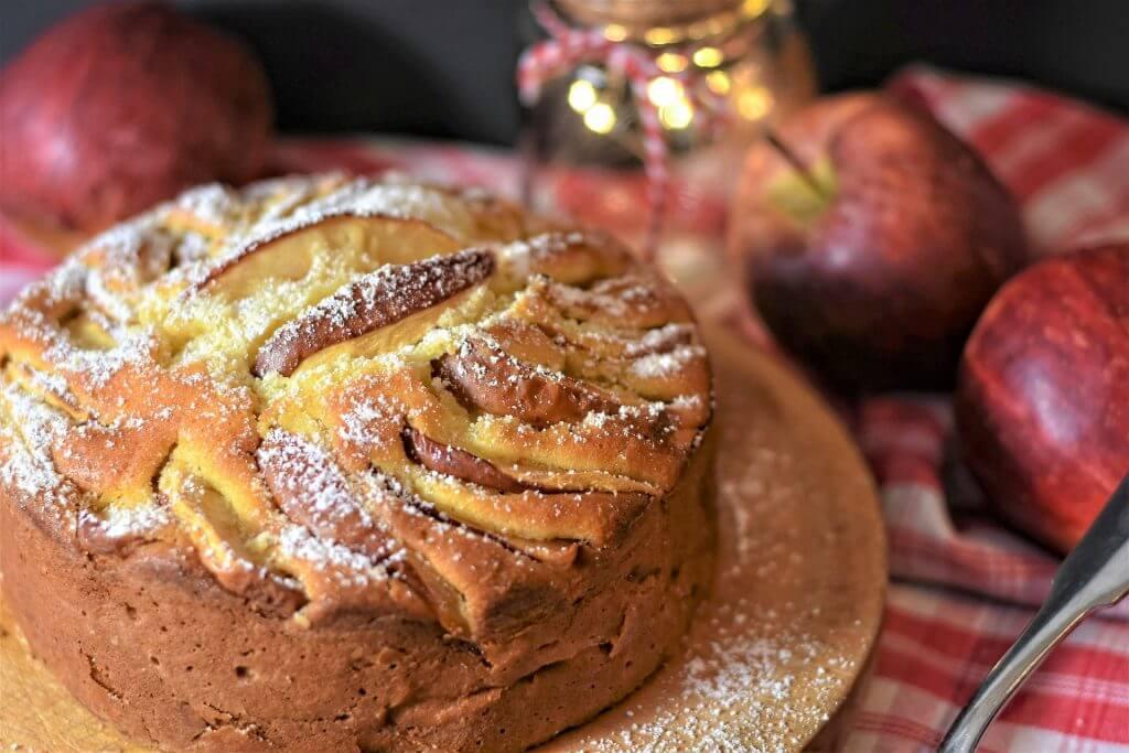 gâteau aux pommes accompagné de pommes rouges sur une table avec une nappe à carreaux